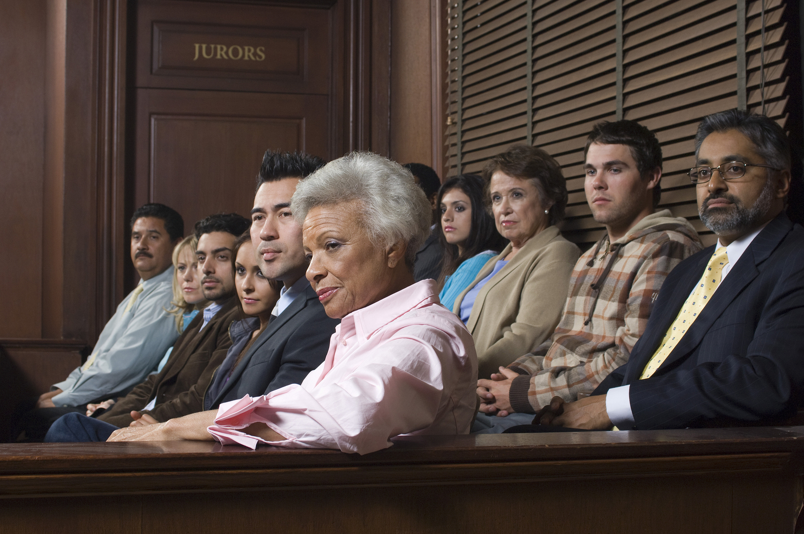 Multi ethnic jurors in witness stand of court house