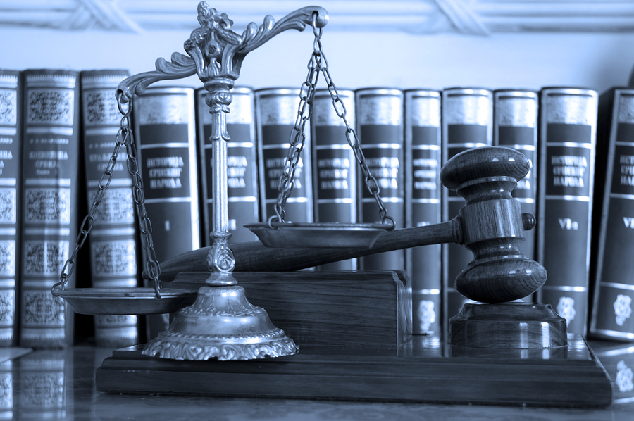Symbol of law and justice with books law and justice concept focus on the gavel blue tone